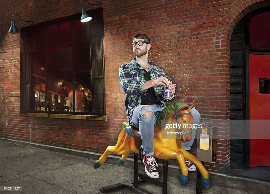 Hipster Man on mechanical horse drinking beer