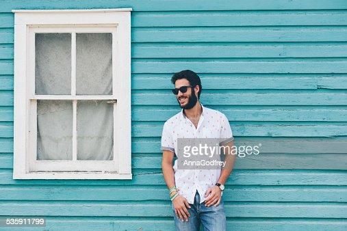 Hipster homem de pé na frente de casa azul : Foto de stock