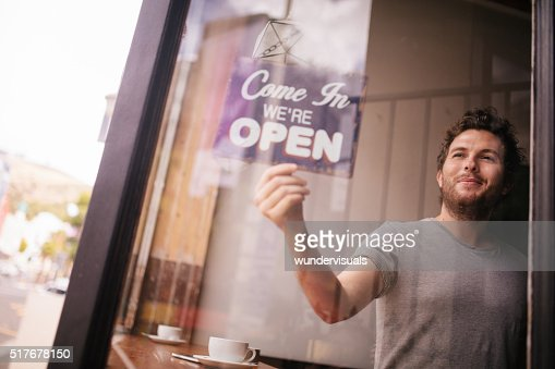 Hipster Man Turning Opening Sign on Door Coffee Shop