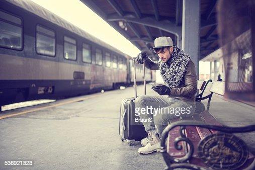 Hipster hombre usando teléfono inteligente en la estación del tren.