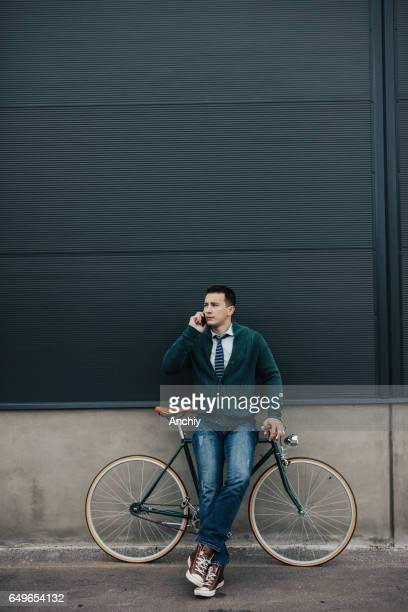 Hipster man with bicycle and smart phone