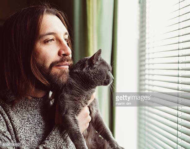 Hipster man with cat looking through the window