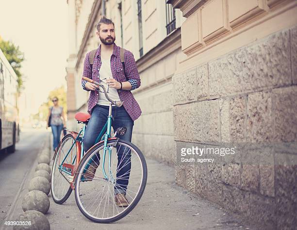 Hipster mand with beard and his  bike outdoors