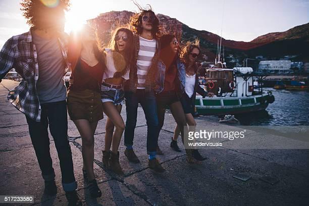 Hipster-multi-ethnischen Freunden zu Fuß am Hafen ein Sonnenuntergang