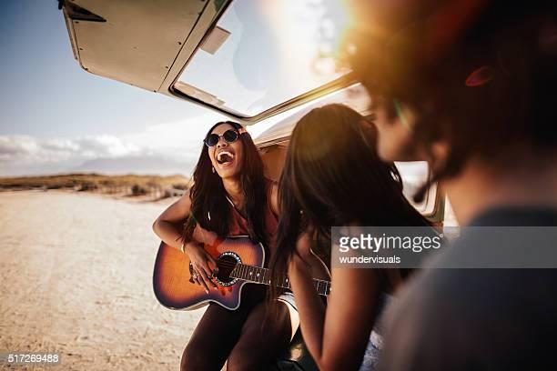 Hipster groupe Multi-ethnique jouer de la guitare sur la plage