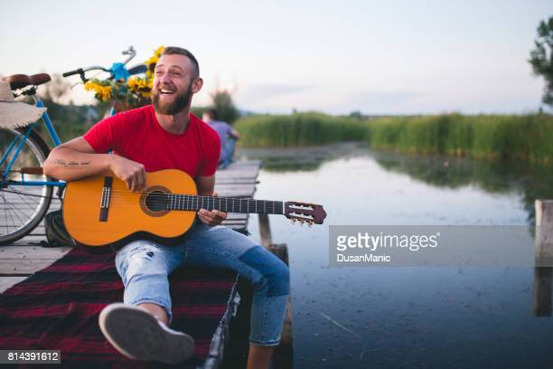 Hipster playing the guitar by the lake