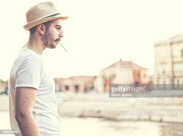 Bas de bikini posant avec un bonnet et une cigarette
