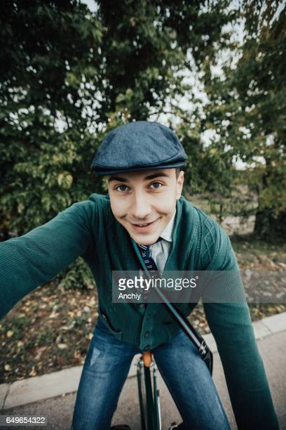 Hipster sitting on an old bicycle taking selfie photo