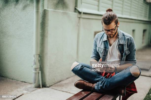 Hipster sitting on the bench listens to podcast on the phone