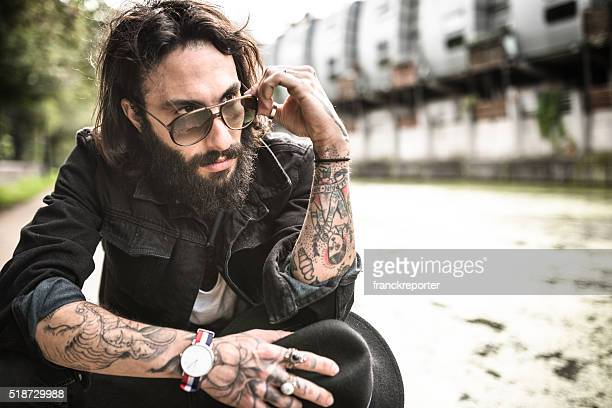 Hipster sitting pensive with tattoo