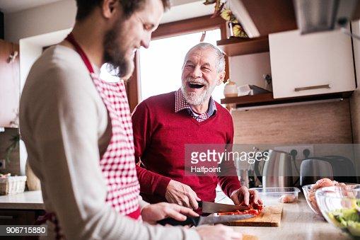 Hijo de hipster con su senior padre cocinando en la cocina. : Foto de stock