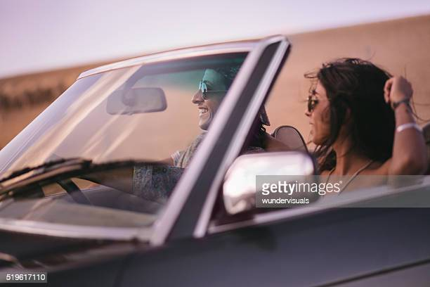 Hipster style teenager couple on a road trip in convertible