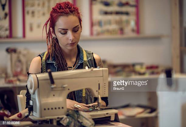 Hipster tailor working on sewing machine in a design studio.