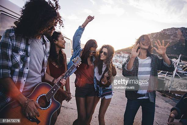Hipster teen friends having fun with guitar on road trip