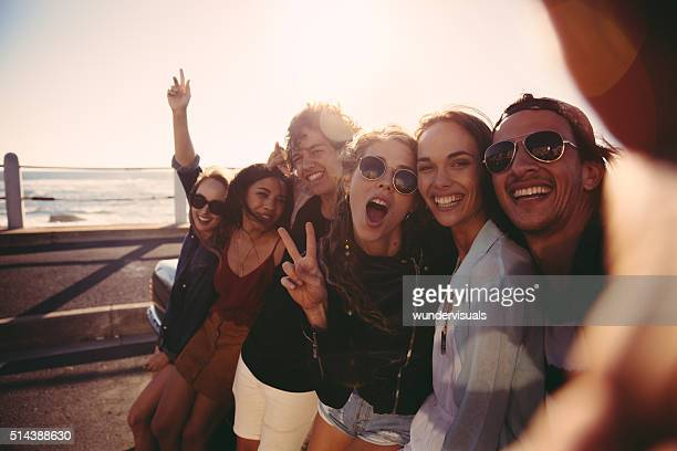Hipster teen friends taking a selfie outdoors at the beach