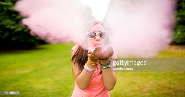 Hipster teenager blowing colorful Holi Powder at camera