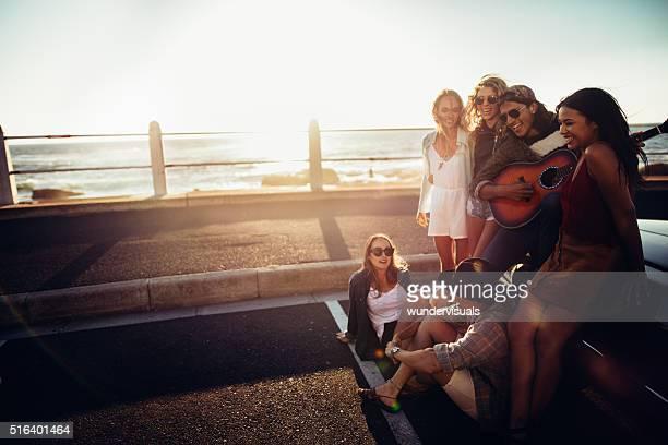Hipster Jugendlicher Freunde feiern am Strand bei Sonnenuntergang mit einer Gitarre