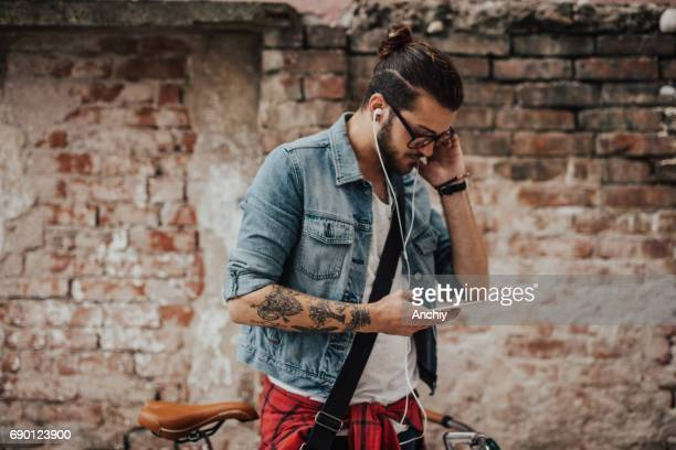Hipster with man bun listens to podcast