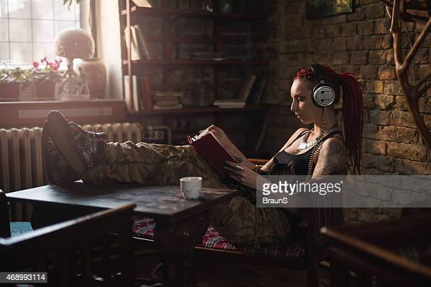Hipster woman reading a book while listening music on headphones.