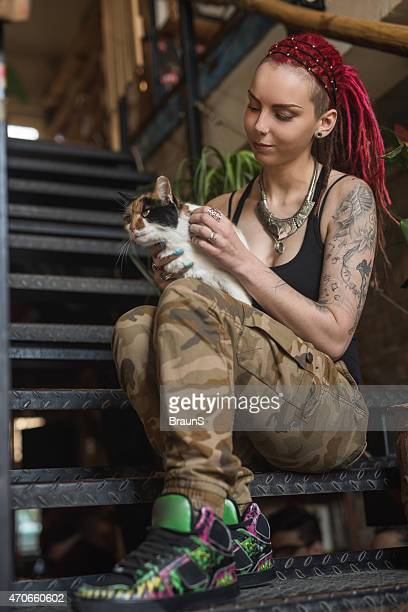 Hipster woman sitting on stairs and enjoying with her cat.