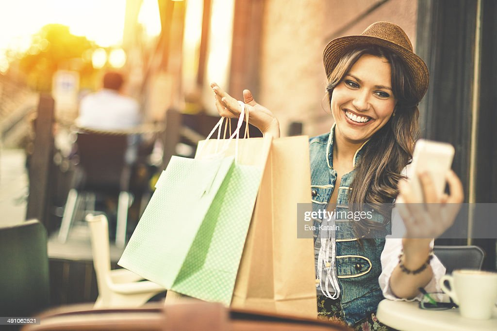 Hipster woman taking selfies with shopping bags in a coffee-shop : Stock Photo