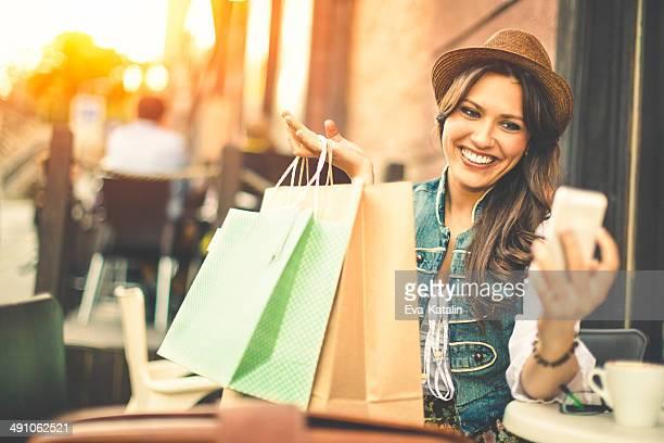 Hipster Frau nimmt selfies mit Einkaufstaschen in einem coffee-shop