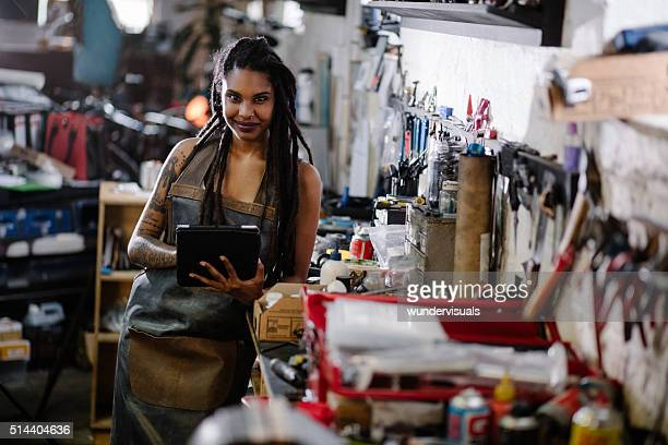 Hipster woman with digital tablet surrounded by tools in worksho