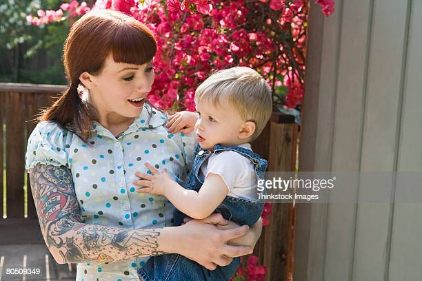 Hipster woman with tattoos and child