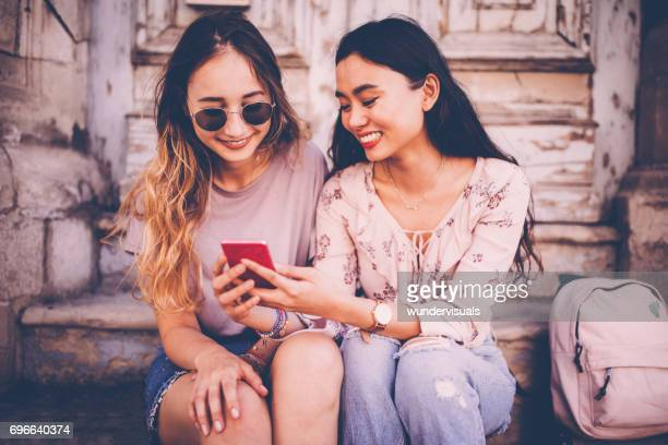Hipster women in old city watching video on a smartphone