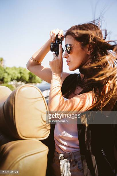 Hipster young adult girl taking a picture from a convertible
