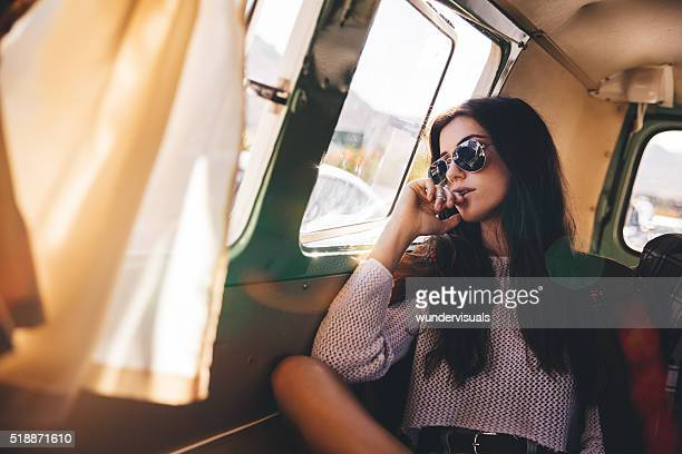 Hipster young woman looking out of a van window