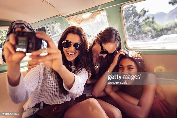 Hipster young women taking selfie inside a vintage van