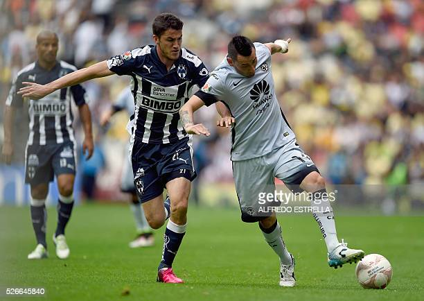 Hiram Mier of Monterrey vies for the ball with Rubens Sambueza of America during their Mexican Clausura 2016 tournament football match at the Azteca...