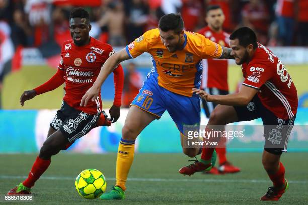 Hiram Munoz and Aviles Hurtado of Tijuana struggle for the ball with Andre Pierre Gignac of Tigres during the semi final second leg match between...