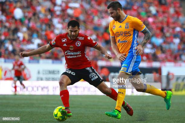 Hiram Munoz of Tijuana struggles for the ball with Andre Pierre Gignac of Tigres during the semi final second leg match between Tijuana and Tigres...