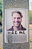 'Hire Me' sign stuck to a lamp post