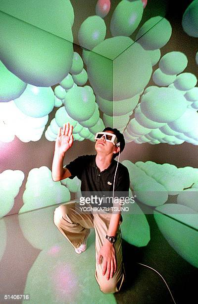 Hiroaki Yano a researcher of the Tokyo University's Intelligent Modeling Laboratory with a 3D glasses extends his hand to touch a carbon atom as he...