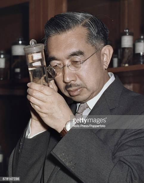 Hirohito Emperor Showa of Japan pictured studying a marine biology specimen through an eyeglass in a laboratory circa 1965