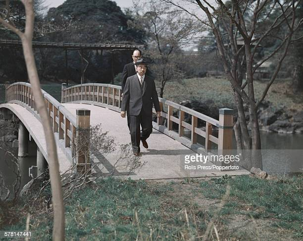 Hirohito Emperor Showa of Japan pictured walking with an aide over a traditional wooden bridge in the Imperial Palace garden in Tokyo Japan in 1965