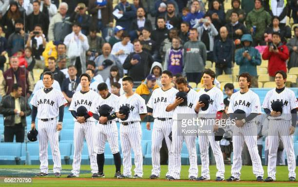 Hiroki Kokubo manager of Japan's World Baseball Classic team and his players sing the national anthem prior to a semifinal game against the United...