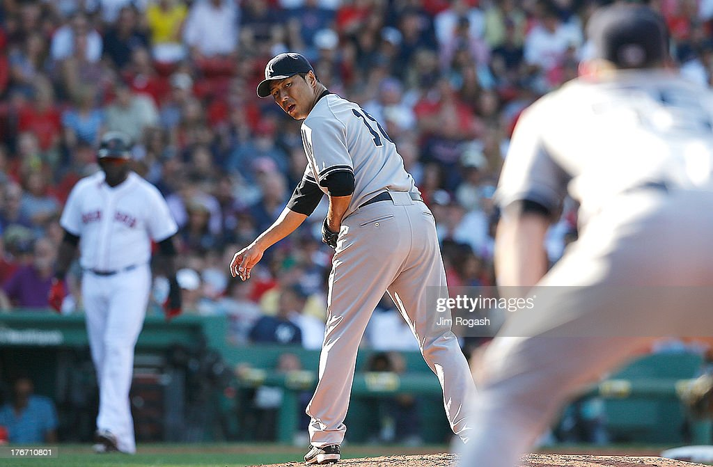 Hiroki Kuroda #18 of the New York Yankees checks the runner at first as David Ortiz #34 of the Boston Red Sox leads from third in the 4th inning at Fenway Park on August 17, 2013 in Boston, Massachusetts.