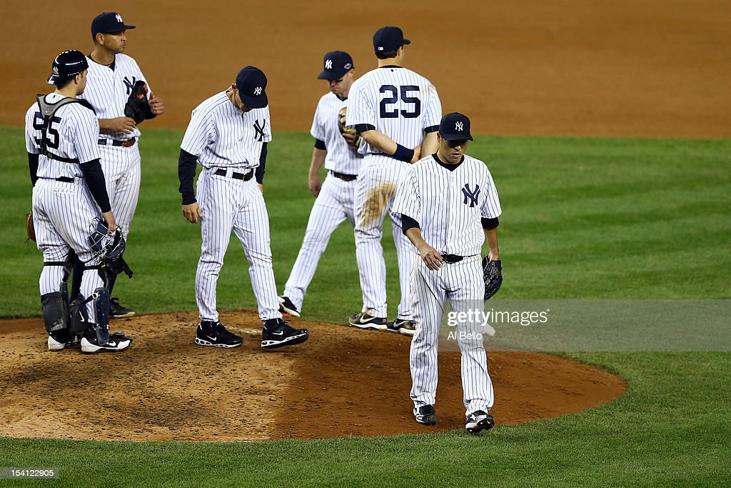 Hiroki Kuroda #18 of the New York Yankees is taken out of the game in the top of the eighth inning by manager Joe Girardi #28 against the Detroit Tigers during Game Two of the American League Championship Series at Yankee Stadium on October 14, 2012 in the Bronx borough of New York City.