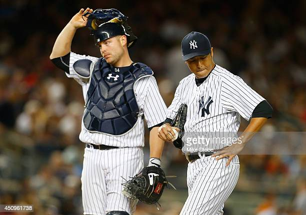 Hiroki Kuroda of the New York Yankees reacts with teammate Brian McCann after giving up the go ahead run in the sixth inning against the Baltimore...
