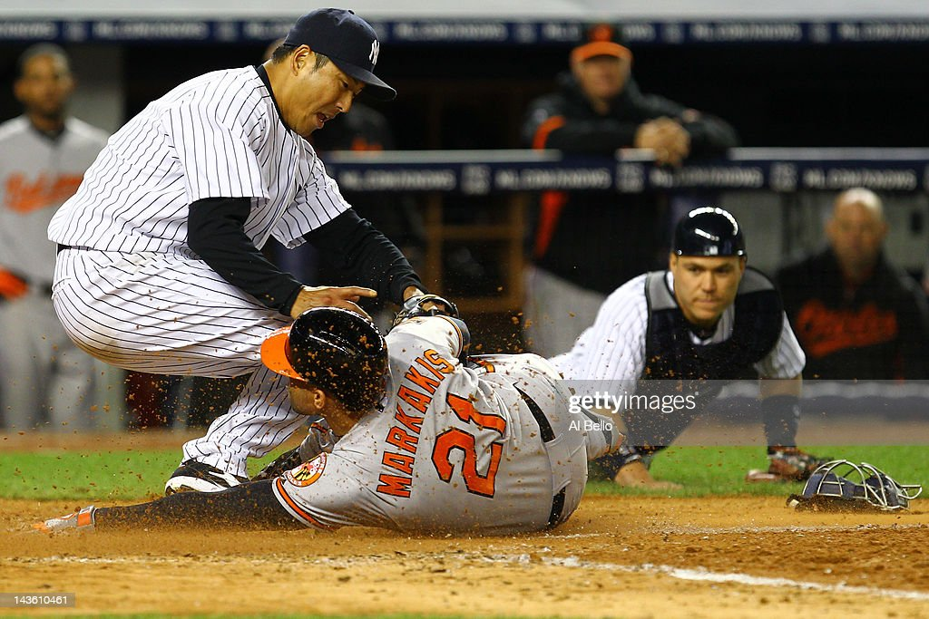 Hiroki Kuroda of the New York Yankees tags out Nick Markakis of the Baltimore Orioles who tried to steal home off of a wild pitch as Russell Martin...