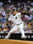 Hiroki Kuroda of the New York Yankees throws a pitch in the top of the second inning during the game against the New York Mets at Yankee Stadium on...