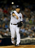 Hiroki Kuroda of the New York Yankees tries to pick off Coco Crisp of the Oakland Athletics in the fourth inning on June 3 2014 at Yankee Stadium in...