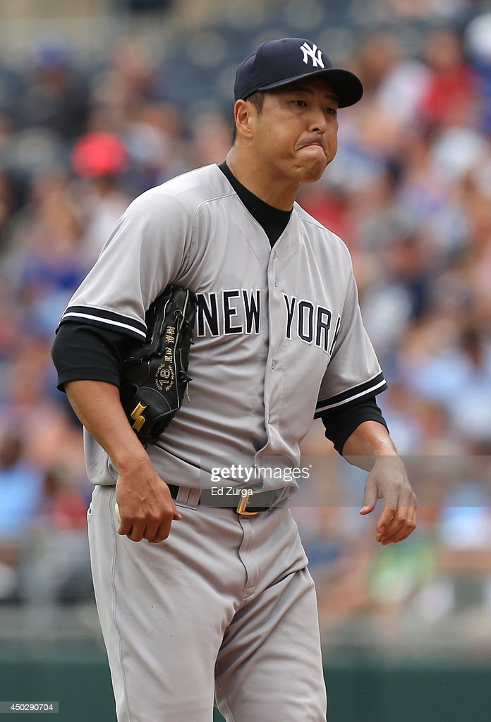 Hiroki Kuroda of the New York Yankees walks to the mound after giving up a single to Alcides Escobar of the Kansas City Royals in the second inning...