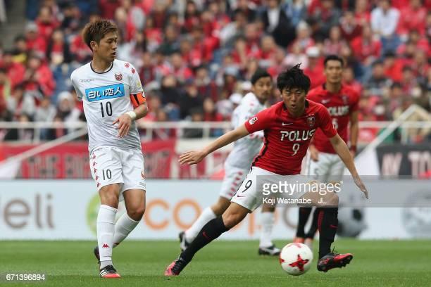 Hiroki Miyazawa of Consadole Sapporo and Yuki Muto of Urawa Red Diamonds compete for the ball during the JLeague J1 match between Urawa Red Diamonds...