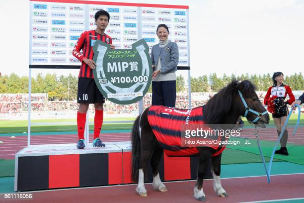 Hiroki Miyazawa of Consadole Sapporo poses with Pony Cicci for photographs during the ceremony after the JLeague J1 match between Consadole Sapporo...