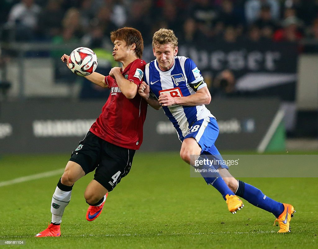 Hiroki Sakai of Hannover 96 is challenged by Fabian Lustenberger of Hertha BSC during the Bundesliga match between Hannover 96 and Hertha BSC at...